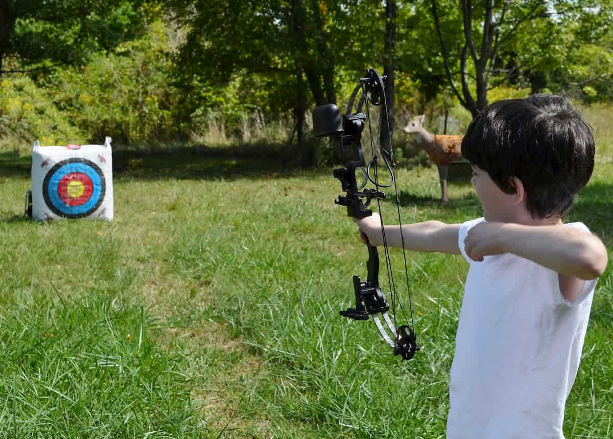 A dark haired boy holds his bow out towards the target as he practices archery on a sunny day - What is the Best Age to Start Archery