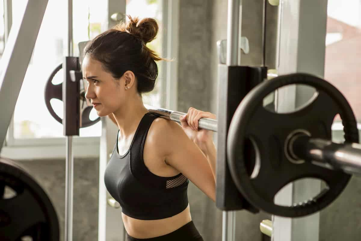 Lady lifting weights in a squat rack - Do You Have to be Strong to do Archery