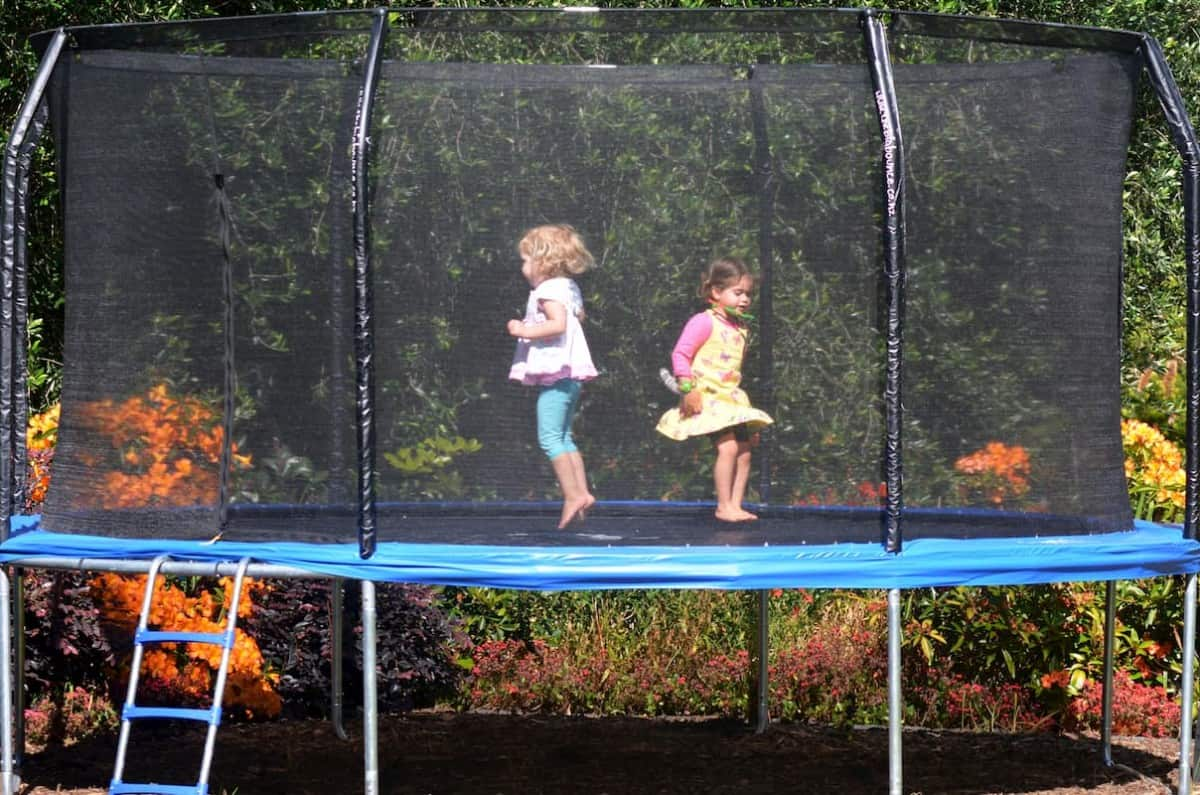 Jumping trampoline with kids in the garden - Trampoline Buyers Guide