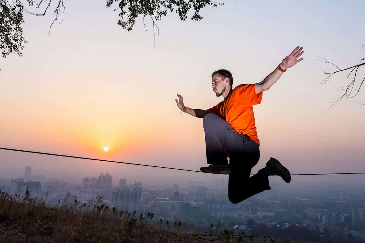 Practicing balance on a slackline while lowered down - How to Get Better at Slacklining