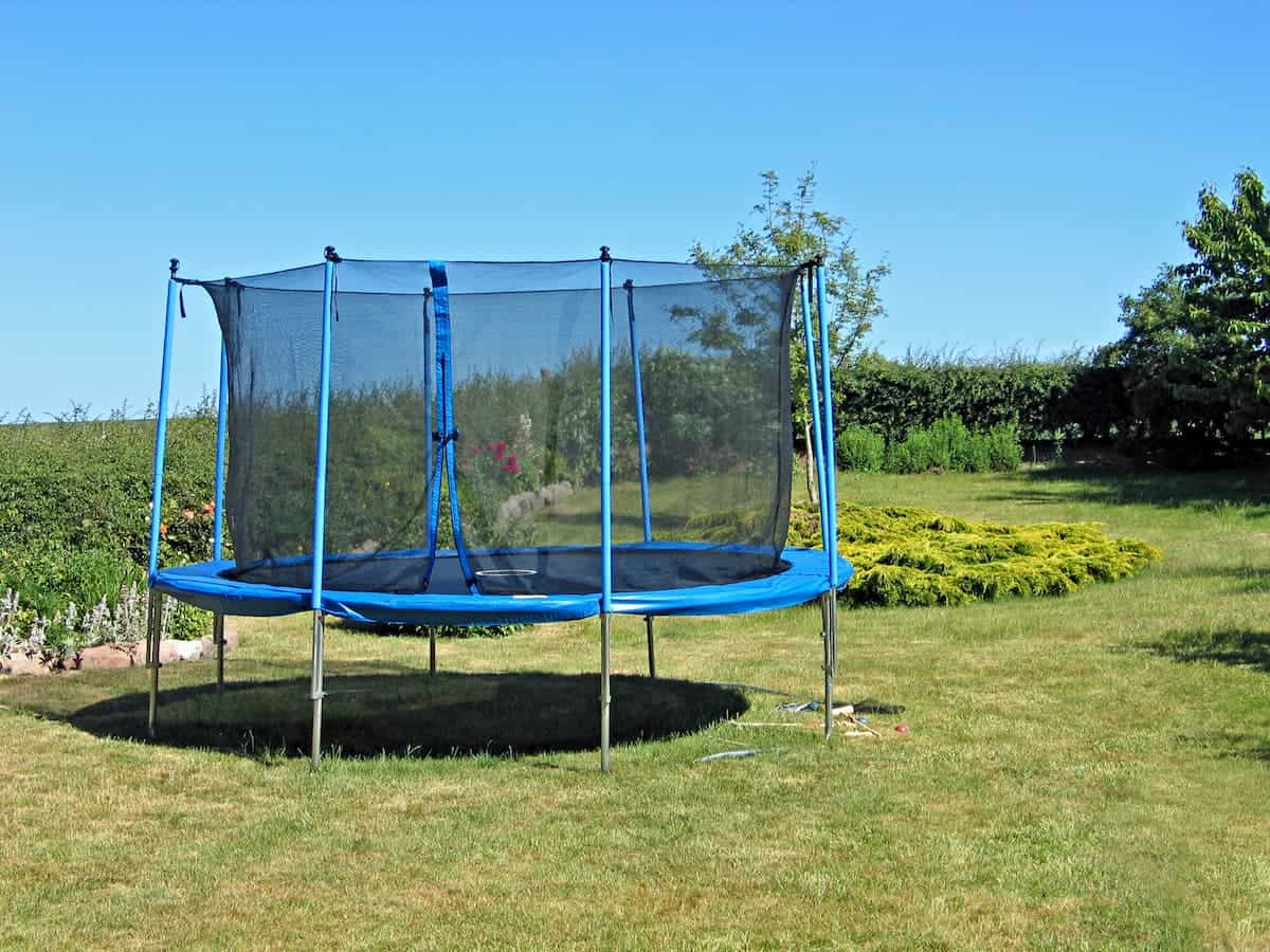 Trampoline in a back yard garden - What Can I Use to Hold a Trampoline Down