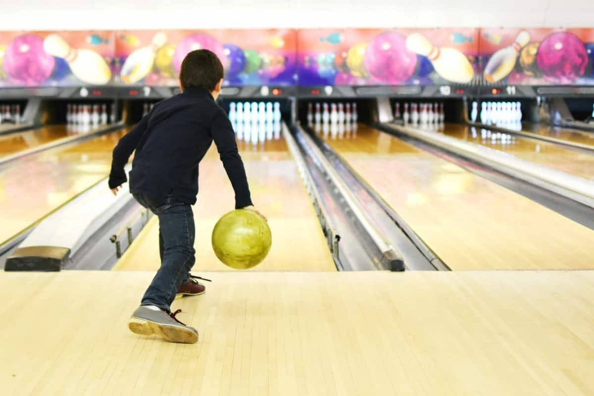 A young boy bowling at a bowling alley - Is Bowling a Sport
