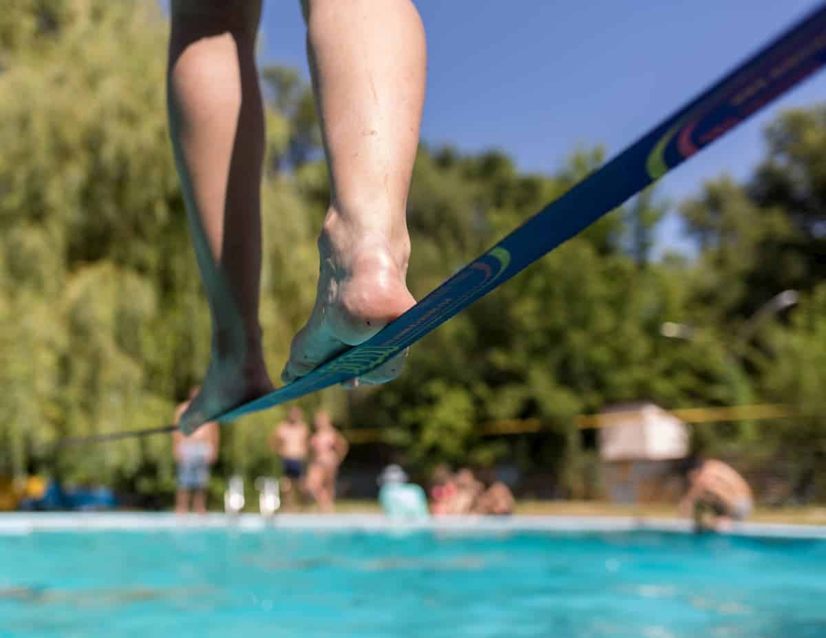 People walk on the slackline over the water - post about Different Types Of Slacklines
